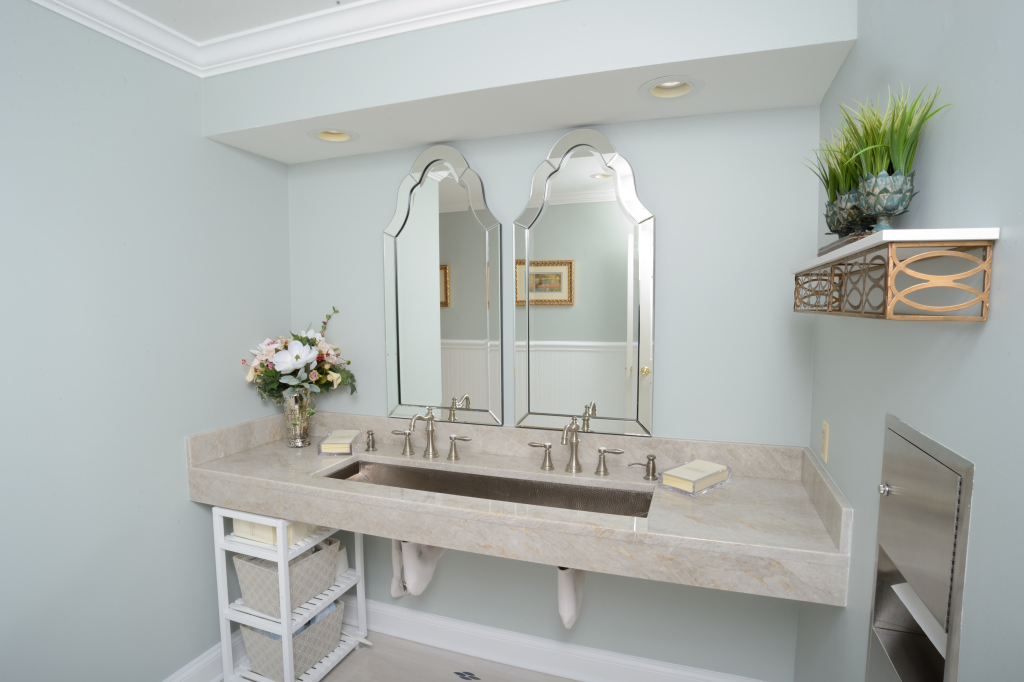 Women's Restroom is a show stopper with wow factors like a hammered copper trough sink, classic Hot/Cold faucet handles and two beautiful beveled, arch mirrors.