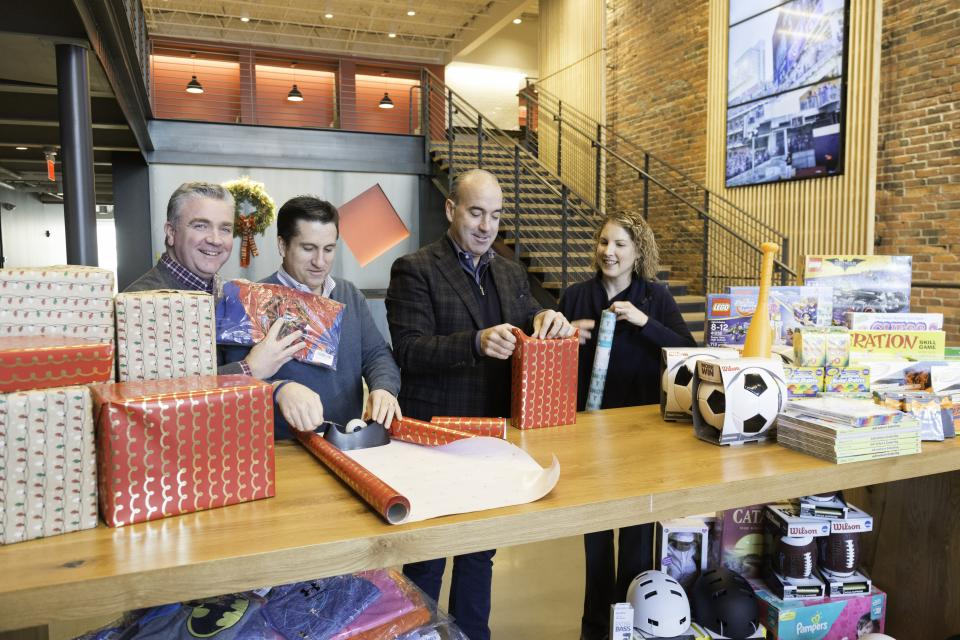 Shawmut executives wrapping presents as part of Shawmut's annual Project Happier Holidays Toy Drive