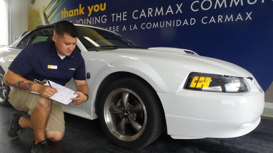 A buyer-in-training hard at work appraising a vehicle.