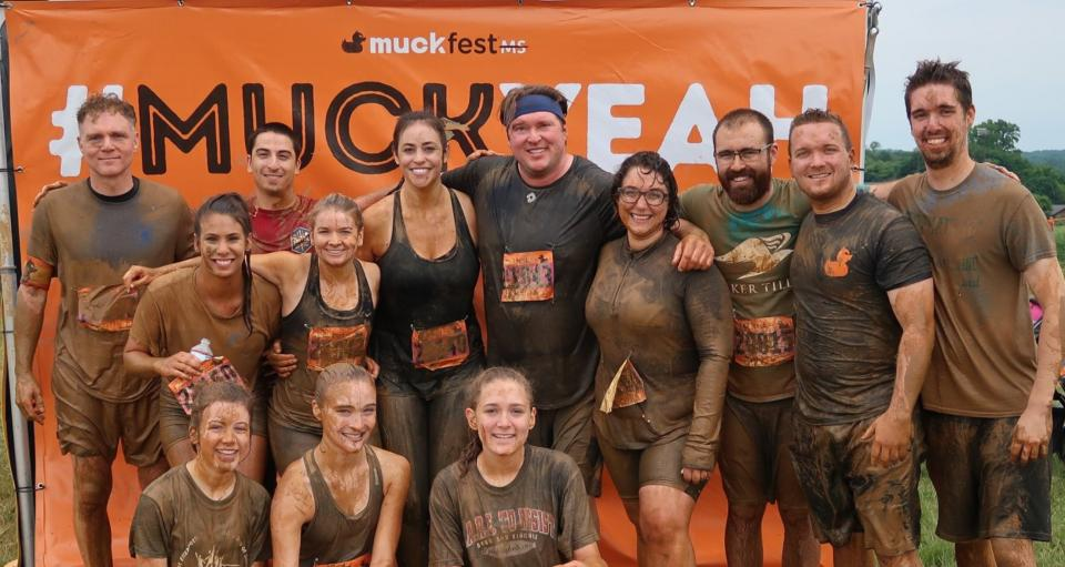 Baker Tilly team members participate in a mud run for charity.