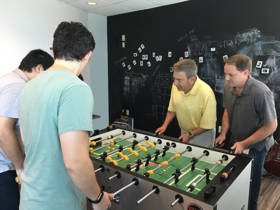Employees at our Atlanta office in the middle of an intense foosball match with CEO Ron Nersesian.