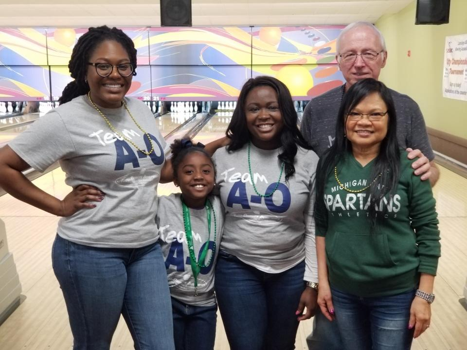 Associates and their families get together for a charity bowling event
