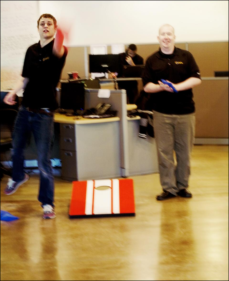 Laughter Playing Corn Hole Bean Bags in the Office