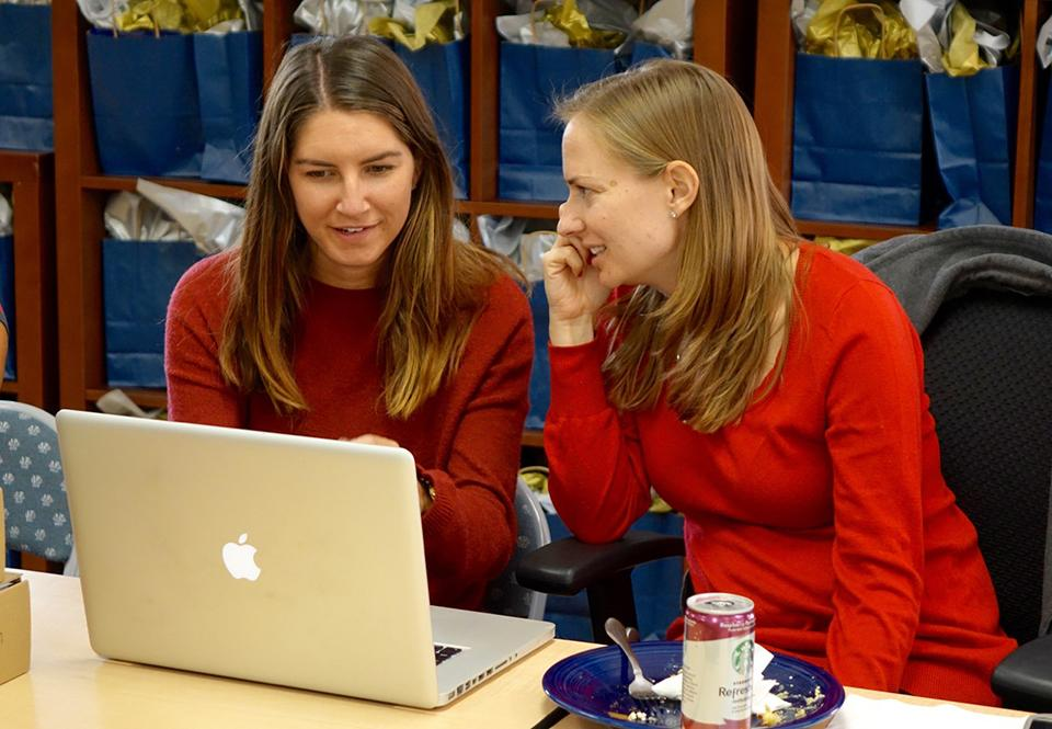 Team members Mara Simon-Meyer and Mariah Cherniss collaborate in the office.