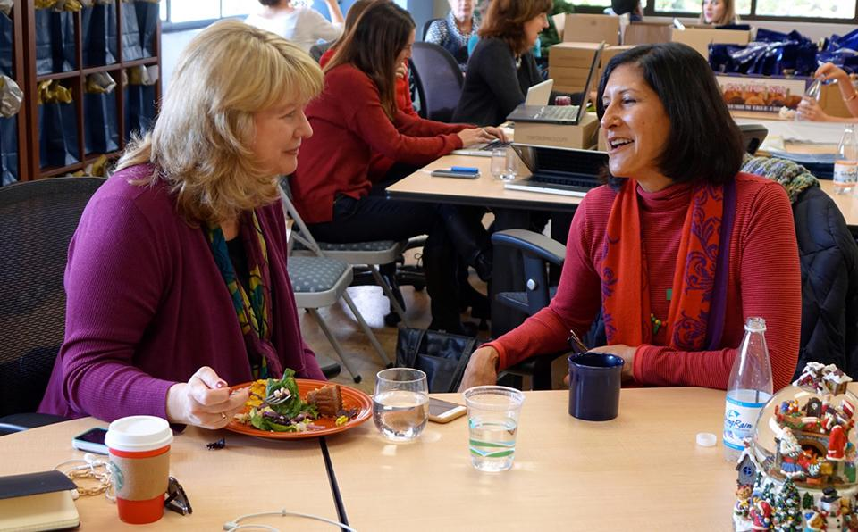 CEO Cheryl Fields Tyler and Consultant Stephanie Denman chat at a Blue Beyond holiday office gathering.