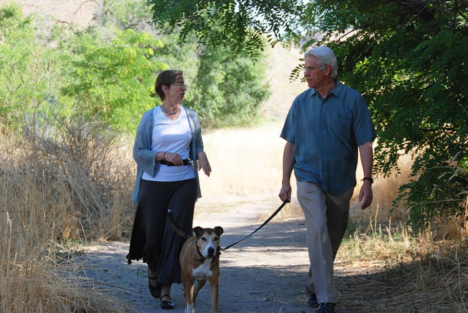 Don Kemper, founder and former CEO, and his wife Molly, former senior vice president of mission, walk their dog Tuva on the Healthwise Boise campus.