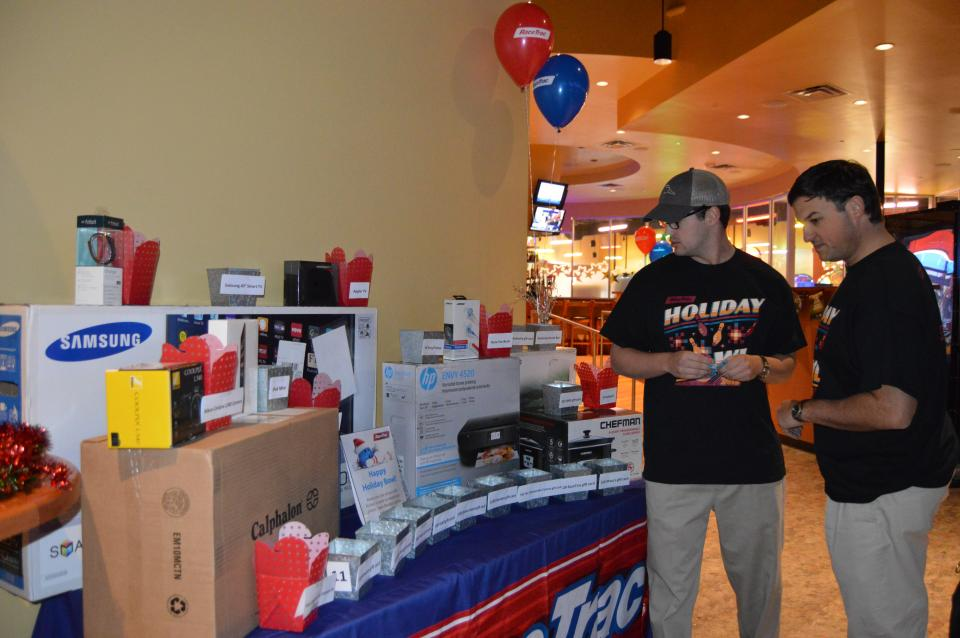Team members eye raffle prizes at the annual Holiday Bowl event.