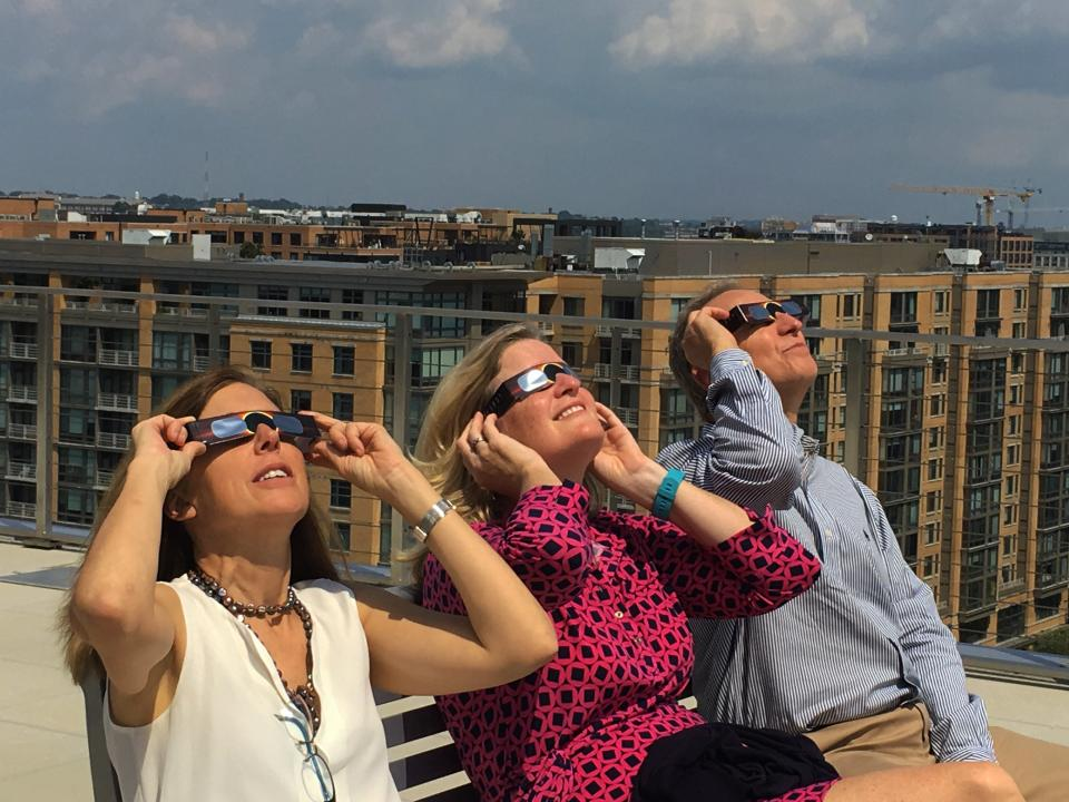 Arnold & Porter Kaye Scholer attorneys, Allison Rumsey, Anne Davis, and Tom Milch, enjoying the view at the Eclipse Party on our rooftop deck.