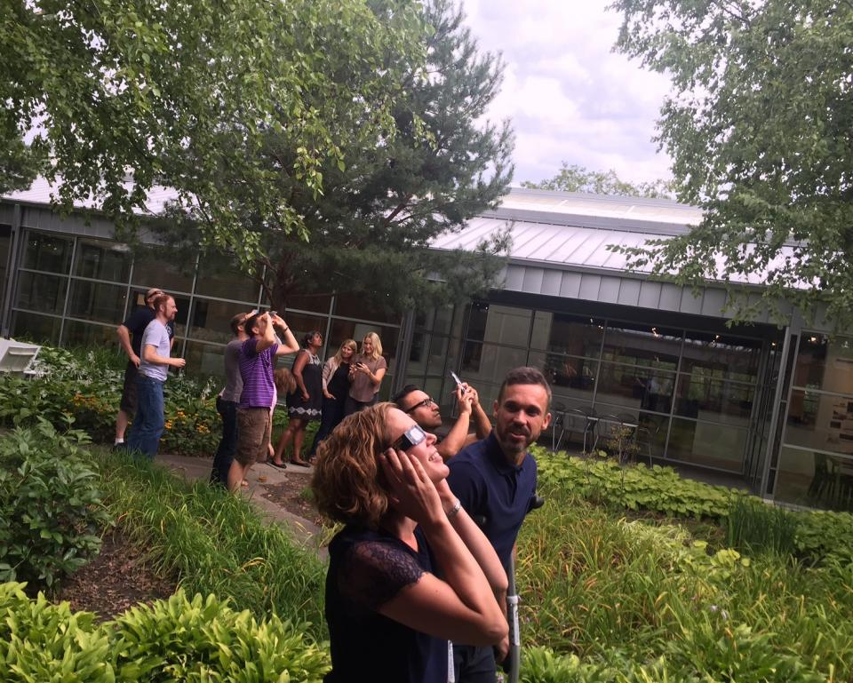 Staff members observe the solar eclipse from the courtyard