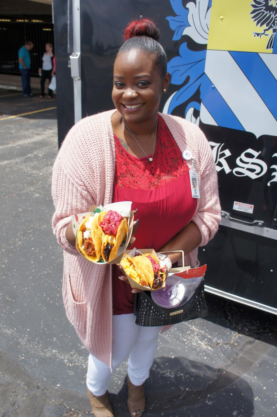 An AF Colleague shows off her tacos from a food truck during a parking lot event.