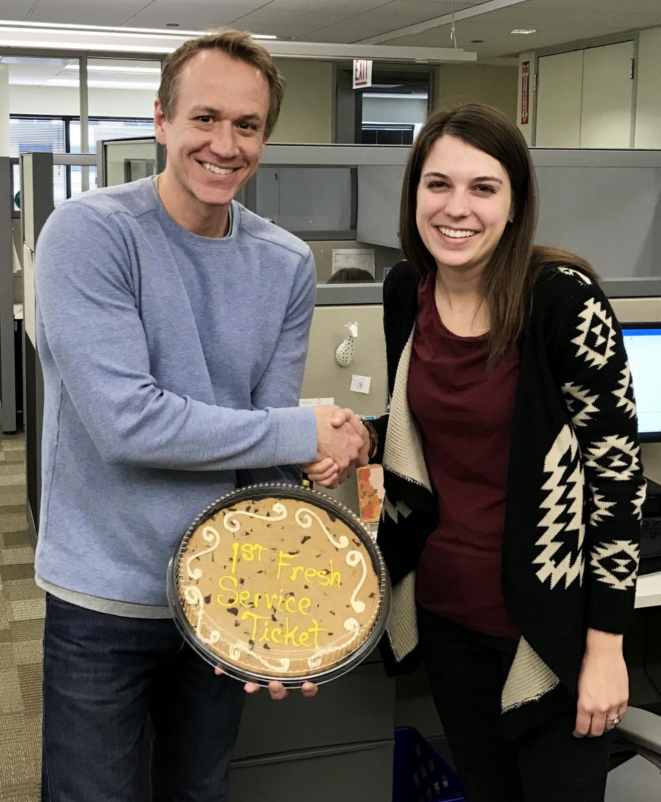An IT manager presents an employee with a cookie cake after she submits the first request for IT assistance using our new ticketing system.