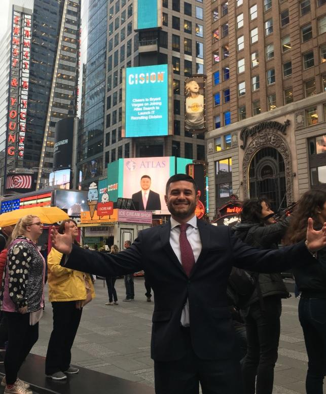 Bryant Vargas in front of our Times Square ad congratulating him on joining the firm