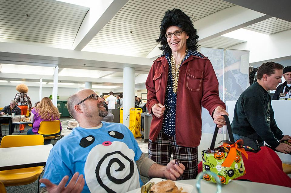 Our Genentech Executive Committee members make it a point to regularly interact with employees, including each year at Halloween. Here our CEO (right) distributes candy while sporting disco themed attire.
