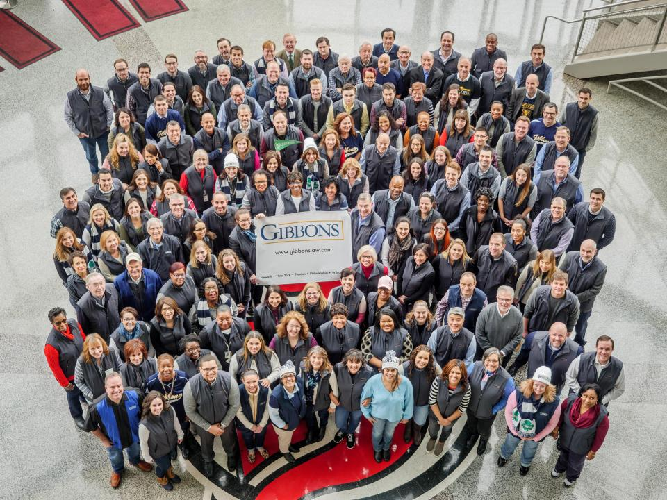 Employees of the firm gather to take a photo to celebrate the firm's recognition as a great place to work by various organizations.