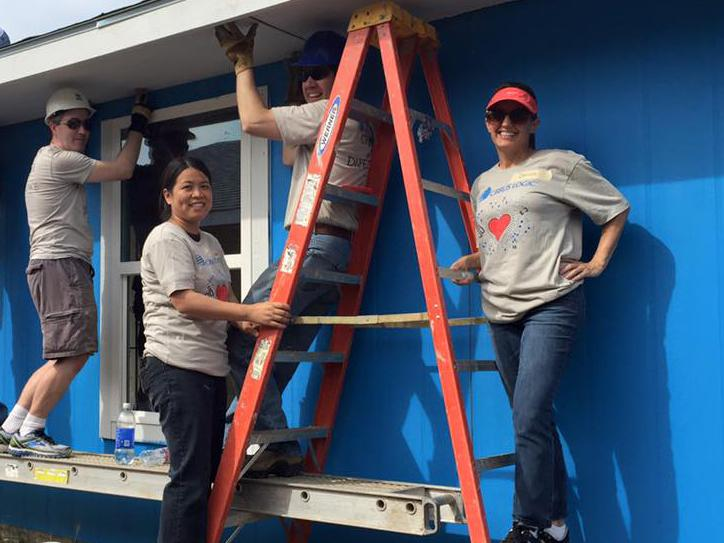 Employees take time out from work to help build a home for Habitat for Humanity.