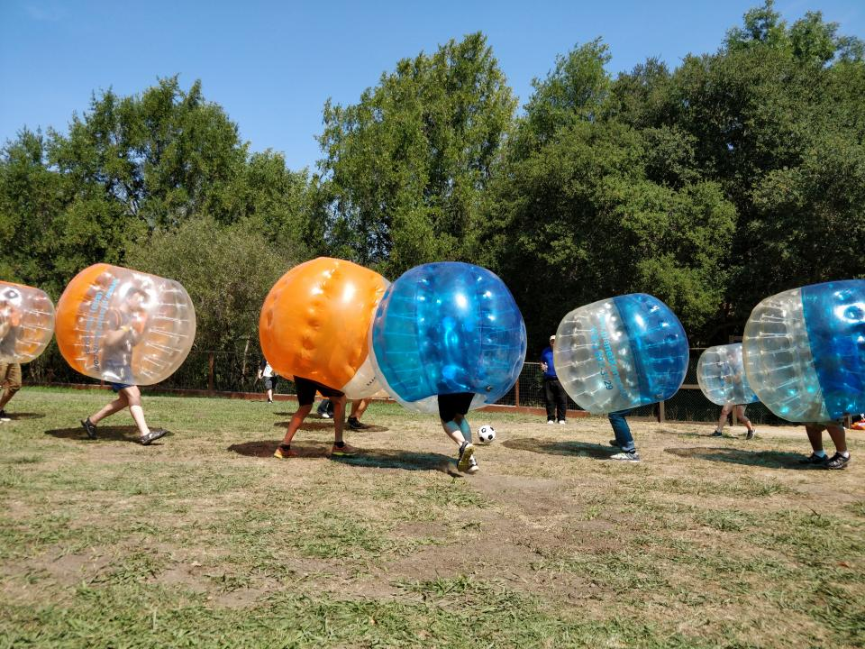 SG teammates and their family members compete in bubble soccer at our annual summer family picnic.