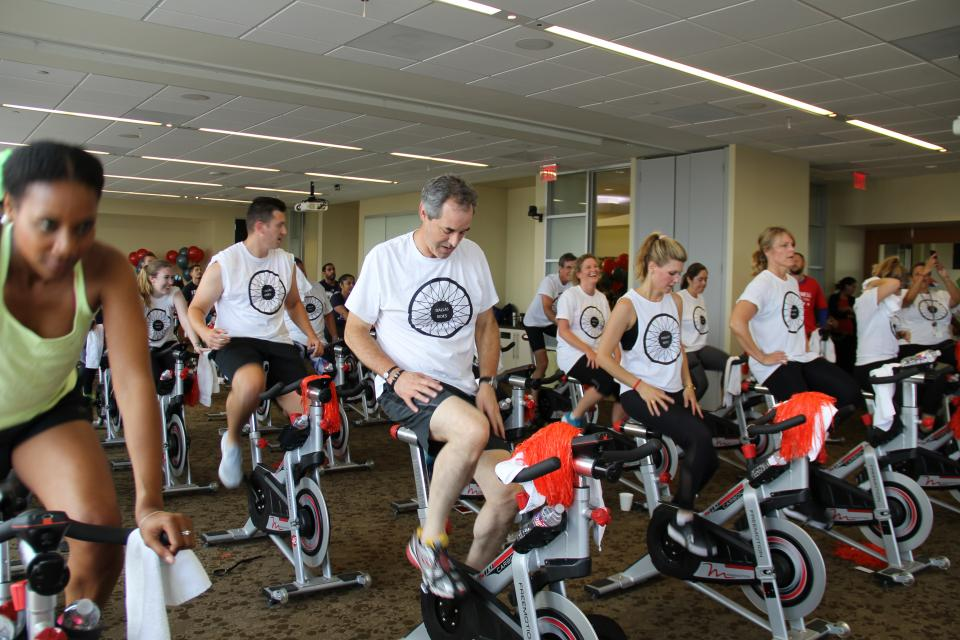 Associates cycling together in wellness event