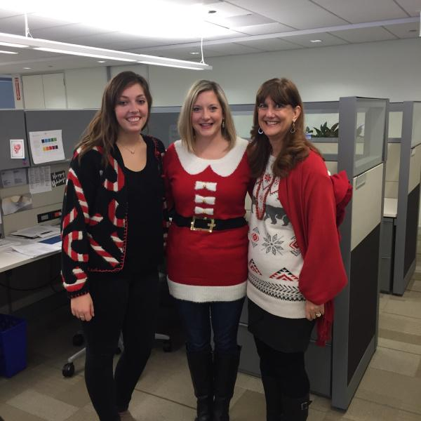 Marketing team members pose wearing holiday sweaters before the APICS Holiday celebration begins.