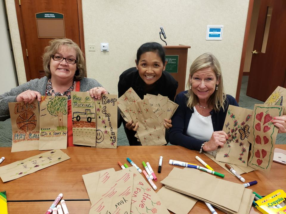 Employees decorating lunch bags for our charity partner.