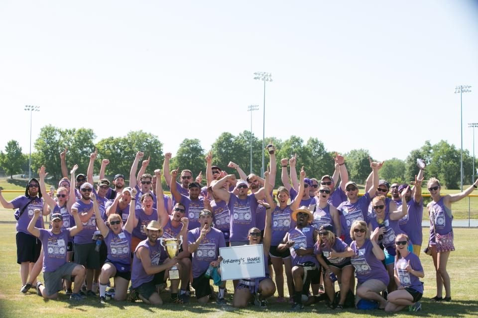 Employees on the purple team celebrate winning 1st place at the annual Field Day event. A donation was made to the local organization Granny's House in their name as part of the prize.