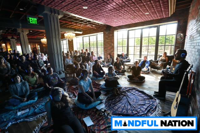 Employees practice meditation and mindfulness techniques during a Mindful Nation session.