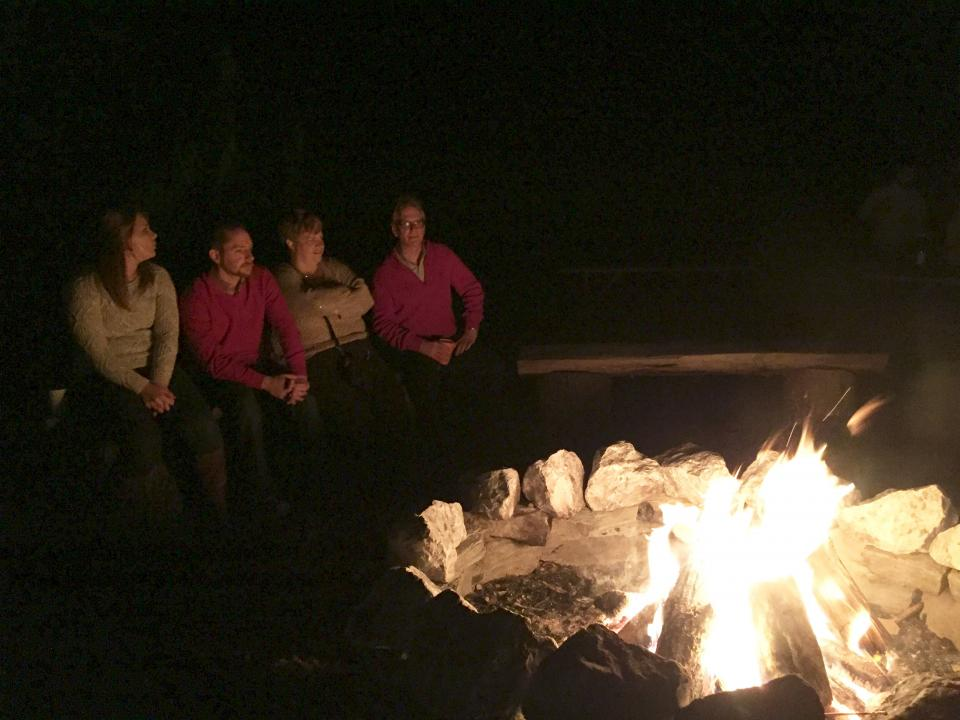 Employees gather around the fire at a company outing to keep warm and share stories.