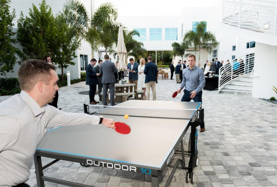 Employees gather in beautiful outdoor areas with modern recreational amenities such as ping pong tables.