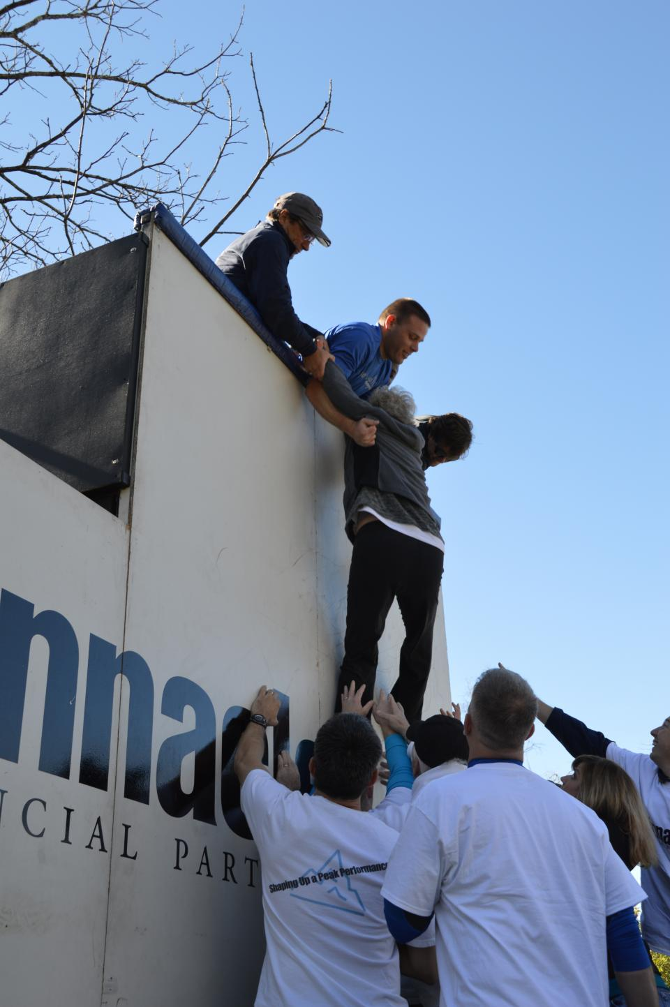 As part of their team building exercises during a three-day cultural orientation with the CEO, new Pinnacle associates scale a 12-foot flat wall, an impossible task without the help of teammates.