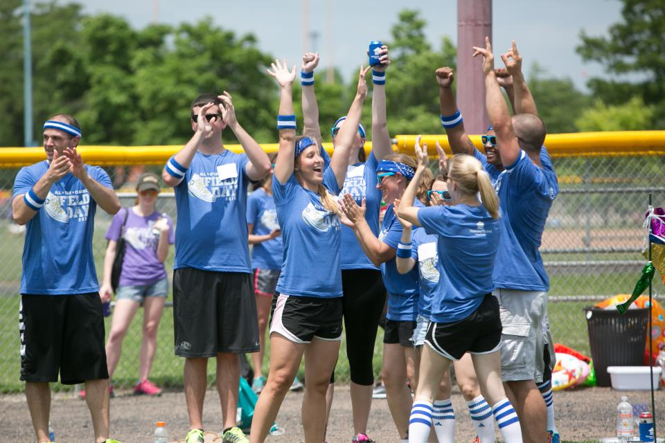 Employees on the blue team celebrate a victory at the annual Field Day event.