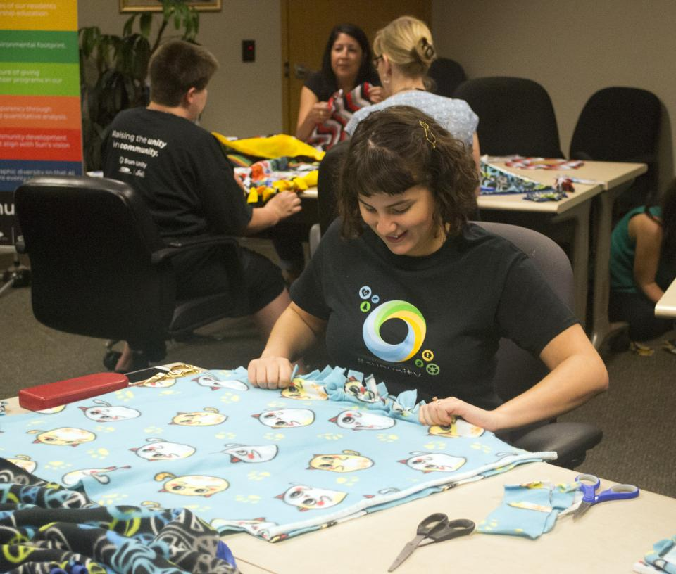 Animal loving team members making blankets and toys for a local animal shelter