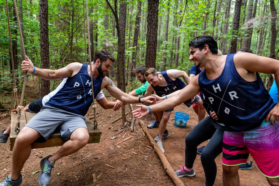 Employees work to complete a team building challenge on a low ropes course as part of the company's leadership conference