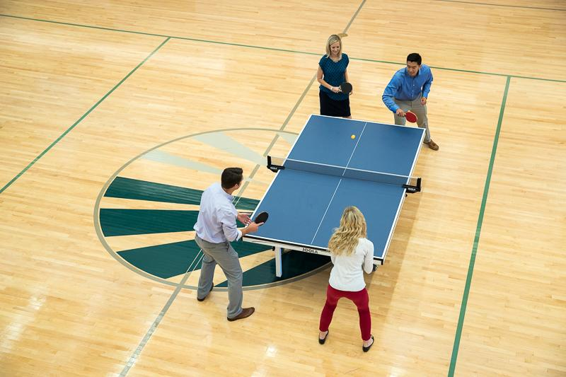 Employees taking a break over a game of ping pong in The Core, our state of the art on-site workout facility