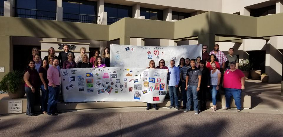 Voya employees in Scottsdale, AZ, pose with the diversity boards that they created.
