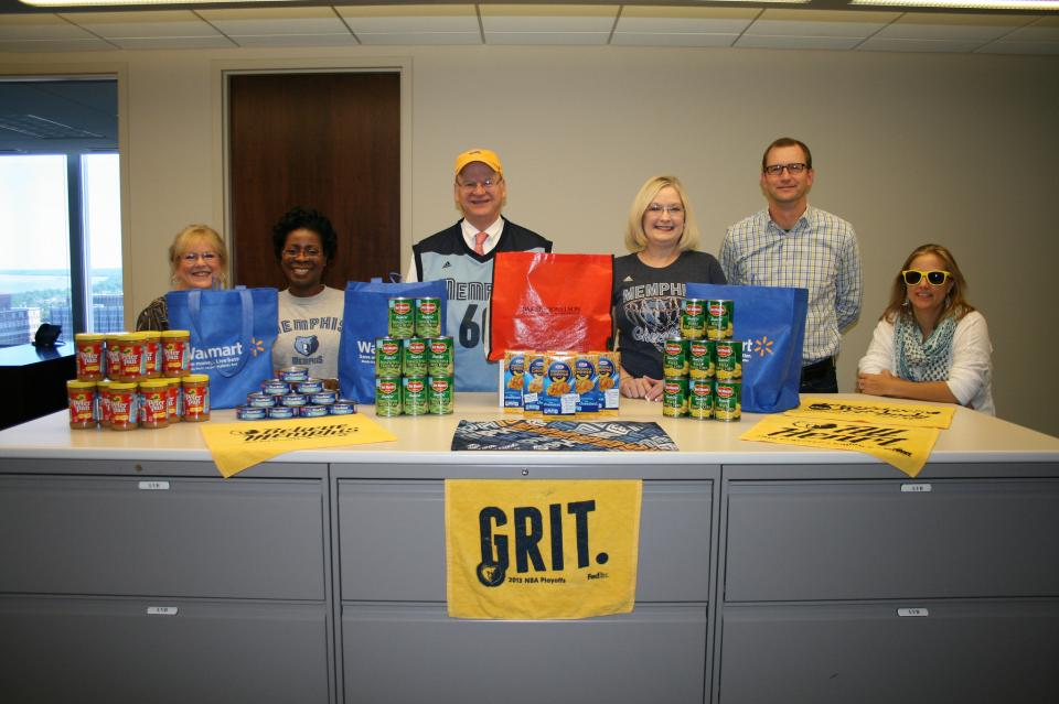 Our CEO is surrounded by fellow Memphis Grizzlies fans and lots of food collected for the local food bank.