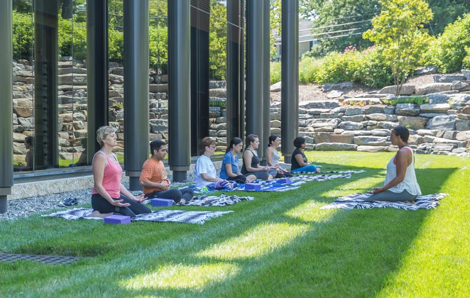 "Recharging your body … – A ""Yoga on the Lawn"" class in Madison, New Jersey, let employees recharge their body and mind. Realogy offers a variety of programs to help maintain a healthy work-life balance."