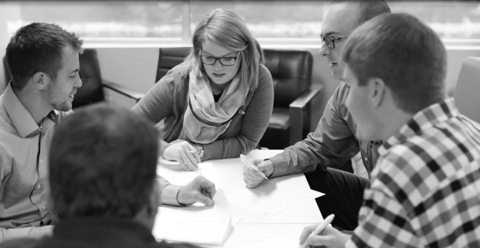 Front L - R: Mark Rooney, Casey Schafbuch, Lauren Brown, Mike Benham, Scott Smith in a strategy meeting