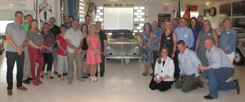 At our 60th anniversary celebration, employees pose with a 1957 Porsche speedster. The car was built the same year that SRC was founded.
