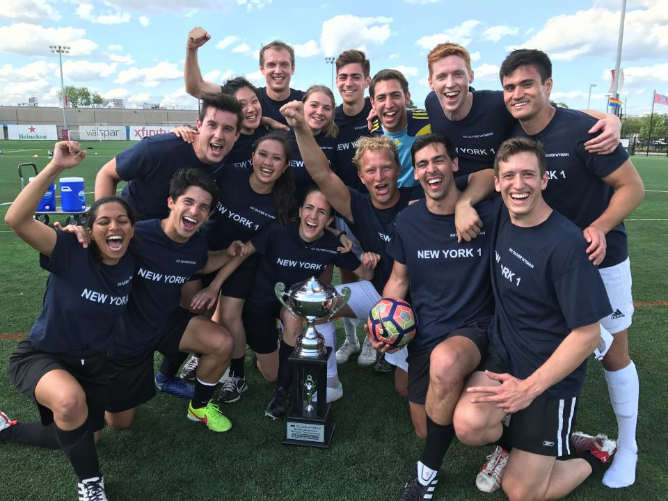 Oliver Wyman North American Soccer Tournament winners posing with their trophy and celebrating their victorious win!