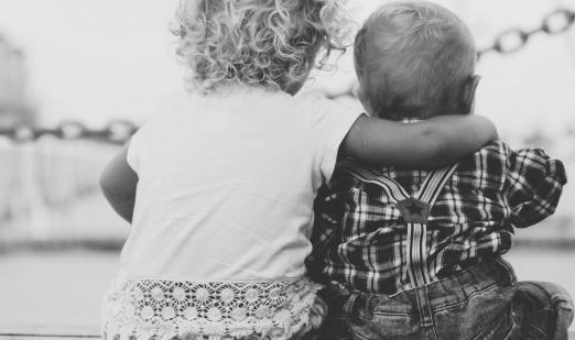 kid sitting with arm around other kid