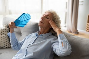 elderly woman waving herself off with a fan to stay cool