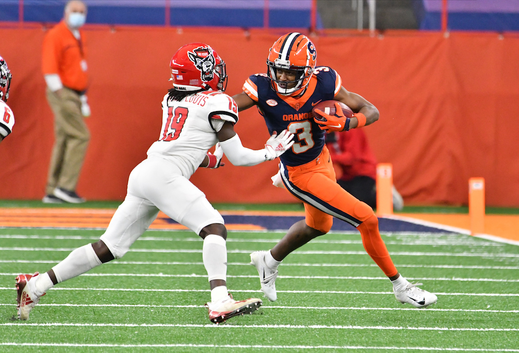 Nov 28, 2020; Syracuse, New York, USA; Syracuse Orange wide receiver Taj Harris (3) tries to avoid a tackle by North Carolina State Wolfpack defensive back Joshua Pierre-Louis (19) in the second quarter at the Carrier Dome. Mandatory Credit: Mark Konezny-USA TODAY Sports