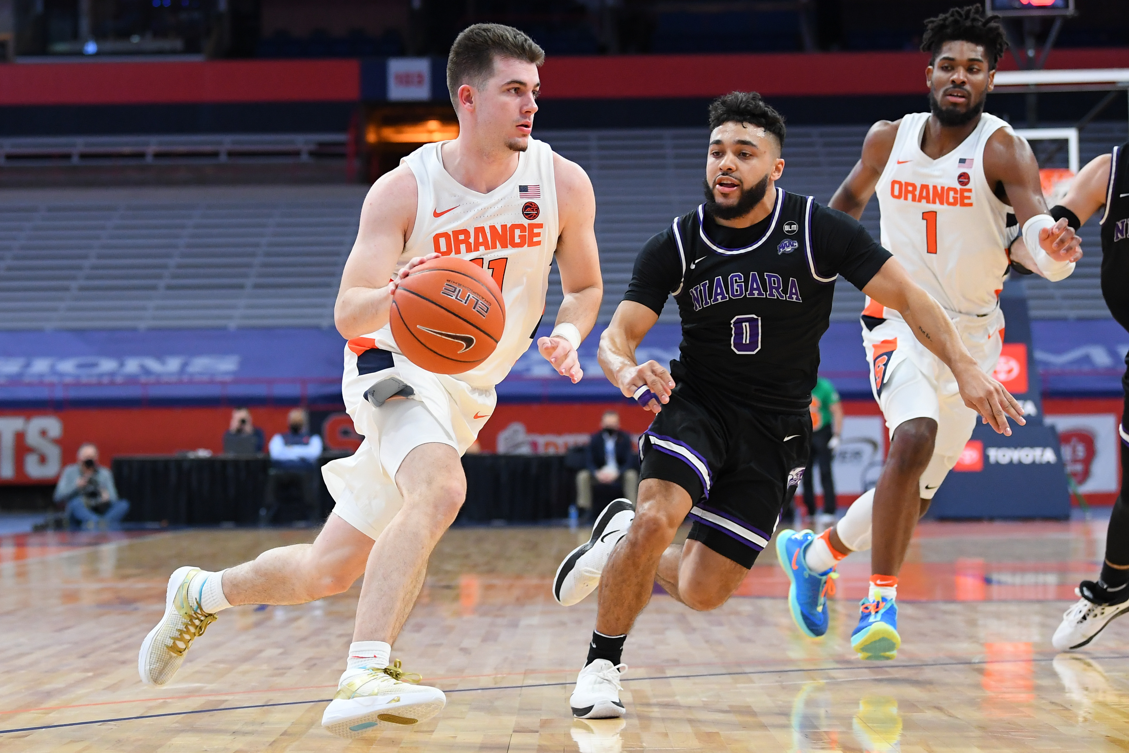 Dec 3, 2020; Syracuse, New York, USA; Syracuse Orange guard Joseph Girard III (11) drives to the basket as Niagara Purple Eagles guard Justin Roberts (0) defends during the first half at the Carrier Dome. Mandatory Credit: Rich Barnes-USA TODAY Sports