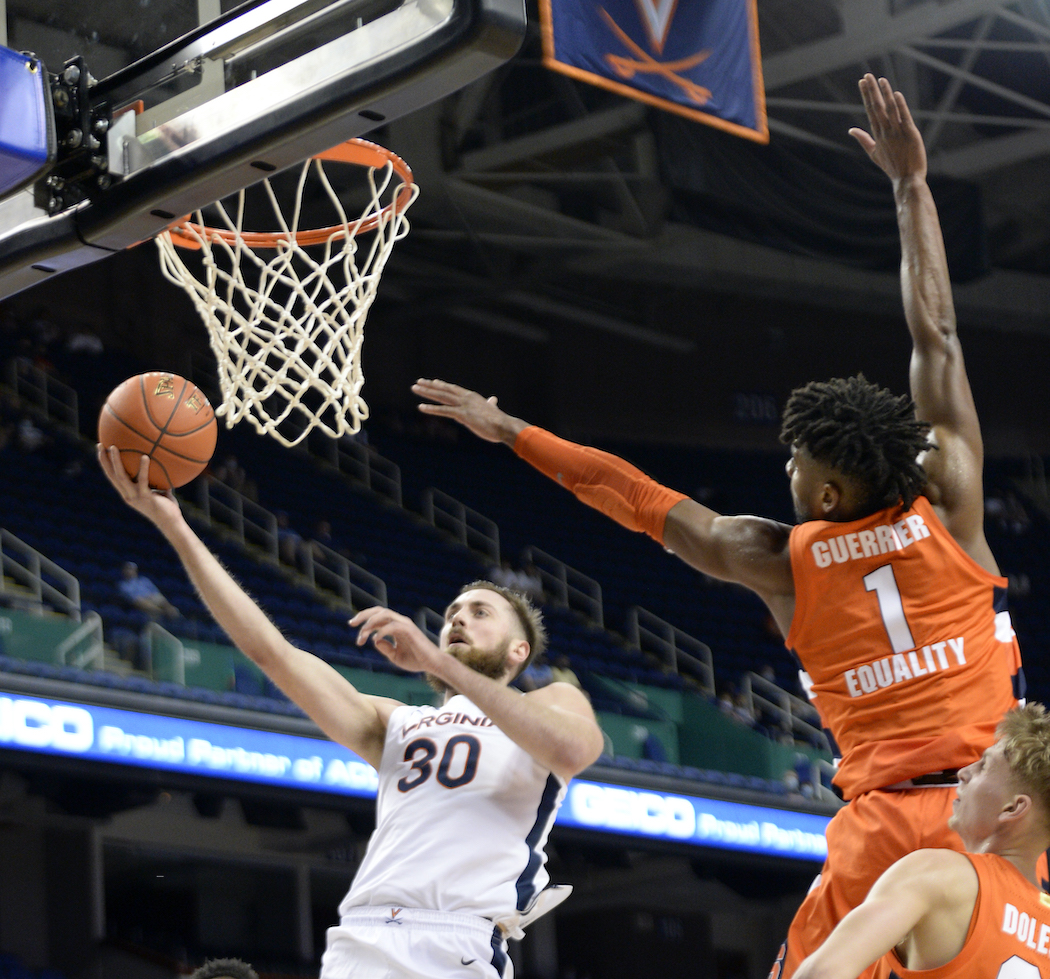 Virginia forward Jay Huff (30) drives around Syracuse forward Quincy Guerrier (1) during the 2021 New York Life ACC Men's Basketball Tournament in Greensboro, N.C., Thursday, March 11, 2021. (Photo by Sara D. Davis, the ACC)