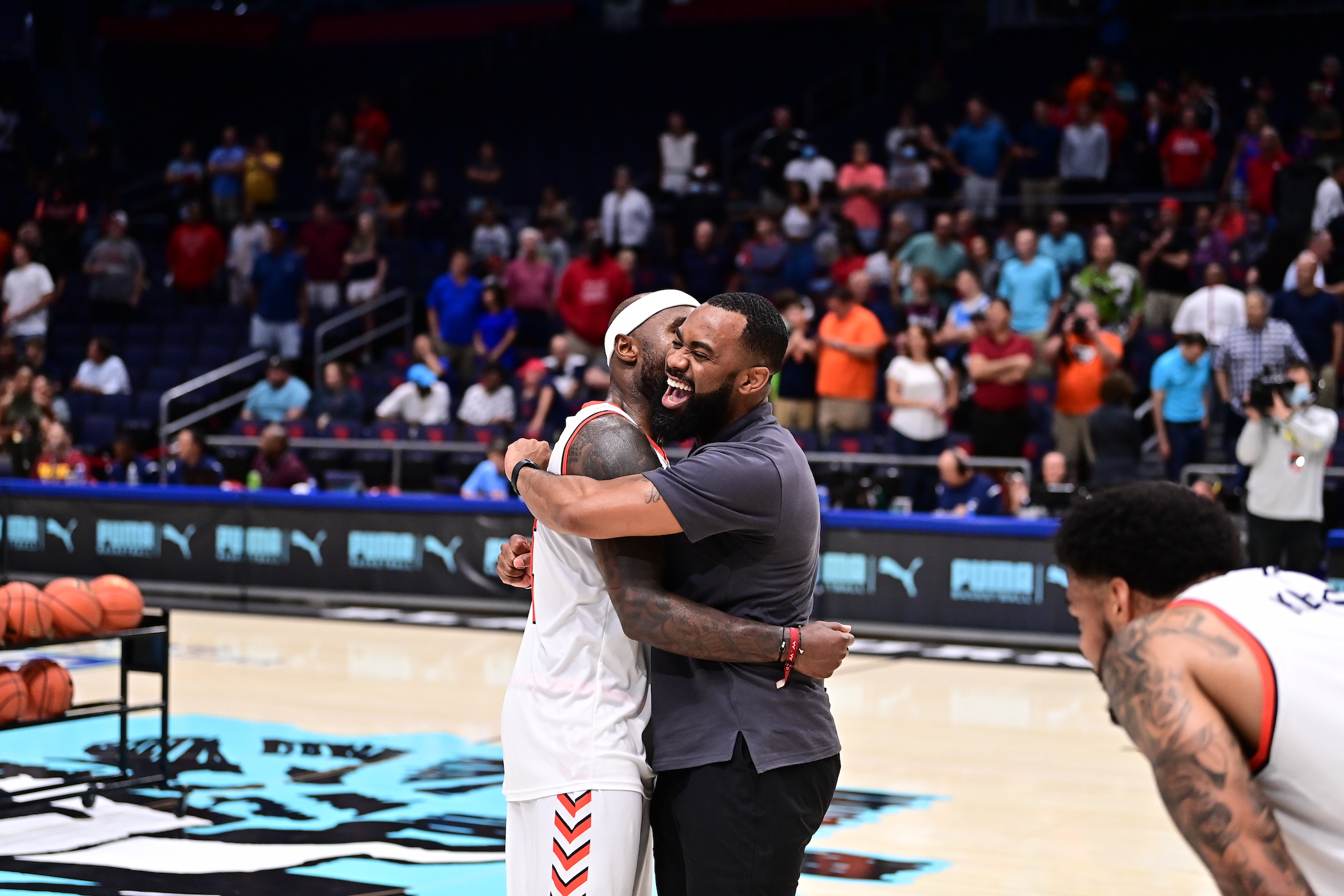 Tyrese Rice and Jeremy Pope hug.