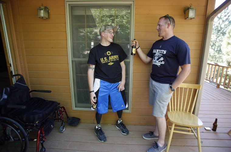 Sgt. Matt Krumwiede (L) relaxes with his twin brother Sgt. Mark Krumwiede as he spends time with friends at home in Pocatello, Idaho, June 30, 2014. Krumwiede was on patrol in Afghanistan in 2012 when he stepped on an improvised explosive device which tore away both his legs, damaged his left arm, and ripped open his abdominal cavity. Since then he has undergone dozens of surgeries and spent time recovering at Brooke Medical Center in San Antonio, Texas, learning to walk again with the use of prosthetic legs. In June 2014, he visited to his hometown of Pocatello, Idaho for the first time since he was injured. Picture taken June 30, 2014. (Jim Urquhart/Reuters)