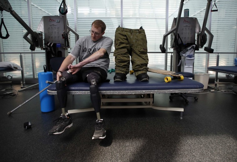 Sgt. Matt Krumwiede prepares to put on prosthetic legs to practice riding his longboard at the Center for the Intrepid at Brooke Army Medical Center in San Antonio, Texas, February 24, 2014. Krumwiede was on patrol in Afghanistan in 2012 when he stepped on an improvised explosive device which tore away both his legs, damaged his left arm, and ripped open his abdominal cavity. Since then he has undergone dozens of surgeries and spent time recovering at Brooke Medical Center in San Antonio, Texas, learning to walk again with the use of prosthetic legs. In June 2014, he visited to his hometown of Pocatello, Idaho for the first time since he was injured. Picture taken February 24, 2014. (Jim Urquhart/Reuters)