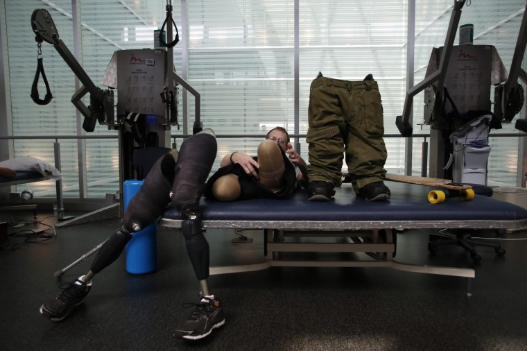Sgt. Matt Krumwiede prepares to put on prosthetic legs to practice riding his longboard, a type of skateboard, at the Center for the Intrepid at Brooke Army Medical Center in San Antonio, Texas, February 24, 2014. Krumwiede was on patrol in Afghanistan in 2012 when he stepped on an improvised explosive device which tore away both his legs, damaged his left arm, and ripped open his abdominal cavity. Since then he has undergone dozens of surgeries and spent time recovering at Brooke Medical Center in San Antonio, Texas, learning to walk again with the use of prosthetic legs. In June 2014, he visited to his hometown of Pocatello, Idaho for the first time since he was injured. Picture taken February 24, 2014. (REUTERS/Jim Urquhart)