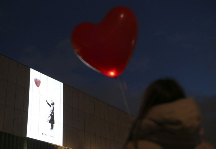 """A spectator holding a balloon looks at a projection of a Syrian refugee girl releasing a red balloon by artist Banksy, a rework of his """"There Is Always Hope"""" graffiti, at the Central House of Artists in Moscow on March 13, 2014. (REUTERS/Sergei Karpukhin)"""