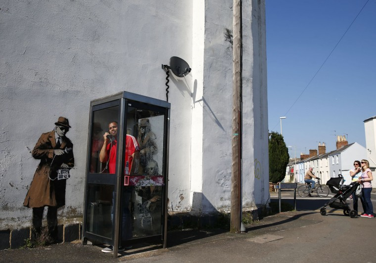 A man stands in a phone box in front of graffiti art on a wall near the headquarters of Britain's eavesdropping agency, Government Communications Headquarters, known as GCHQ, in Cheltenham, western England on April 16, 2014. British media have attributed the new work to acclaimed British street artist Banksy, as a spoof on recent government spying scandals exposed by former U.S. National Security Agency contractor, Edward Snowden, who said that Britain's agency, GCHQ tapped fiber-optic cables carrying international phone and internet traffic and is sharing vast quantities of personal information with the NSA. (REUTERS/Eddie Keogh)