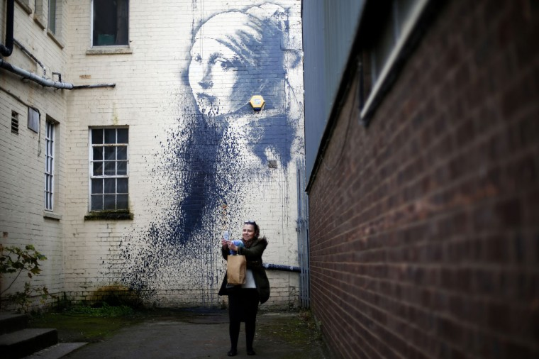 """A woman photographs herself with a piece of street art attributed to Banksy titled """"The Girl with the Pierced Eardrum"""" after it was defaced in an alleyway in Bristol, western England, October 22, 2014. (REUTERS/Andrew Winning)"""